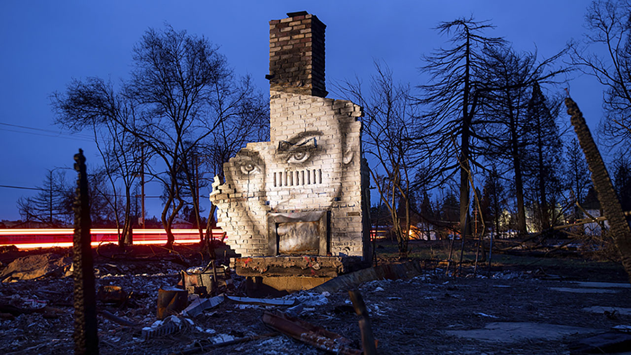 A mural by artist Shane Grammer adorns the chimney of a residence leveled by the Camp Fire in Paradise, Calif.