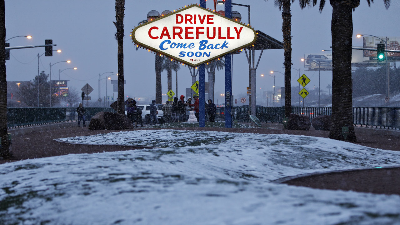 Snow accumulates on a median along the Las Vegas Strip at the Welcome to Fabulous Las Vegas sign, Thursday, Feb. 21, 2019, in Las Vegas.