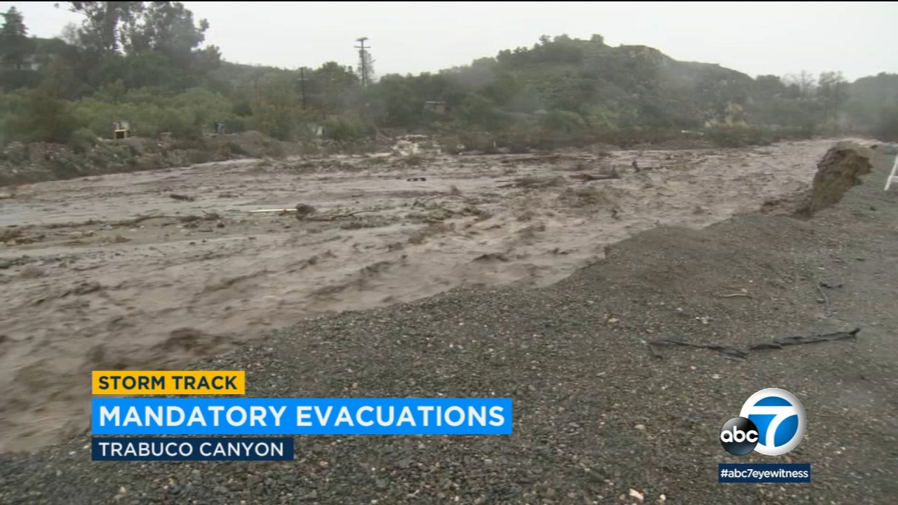 Rain water, mud and debris caused the raging Trabuco Creek to overflow across a bridge amid a strong storm that prompted mandatory evacuations in the area Thursday.