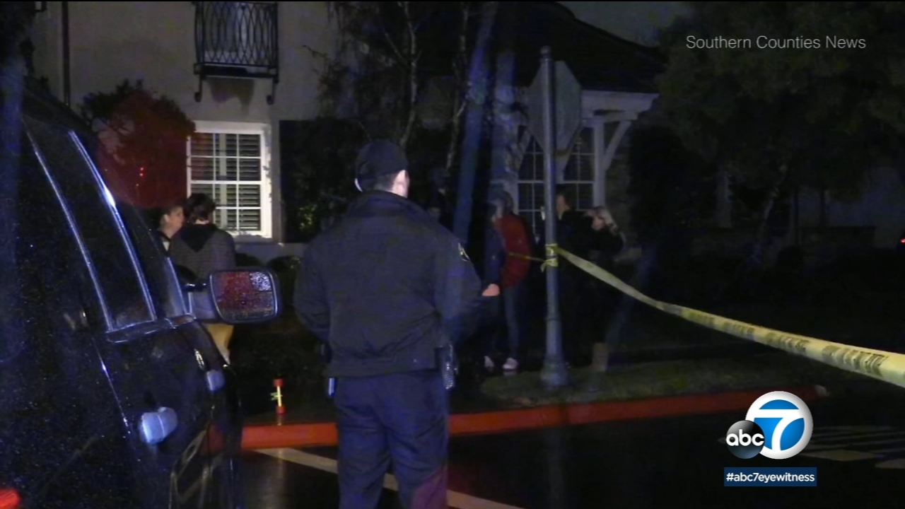 Law enforcement officials are seen in Newport Beach following a triple homicide.