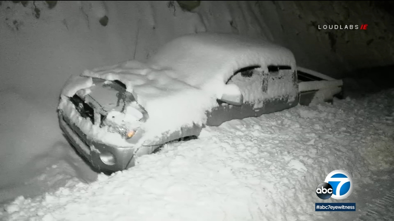 A car is seen buried in snow along State Route 38.