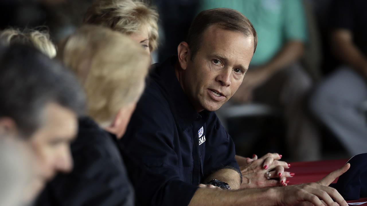 President Donald Trump listens as FEMA Administrator Brock Long, right, speaks Wednesday, Sept. 19, 2018, in Havelock, N.C.