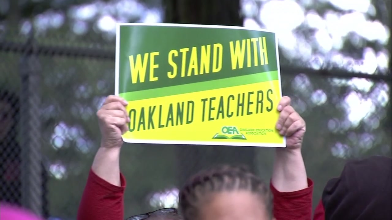 A person holds up a sign supporting teachers in Oakland, Calif.
