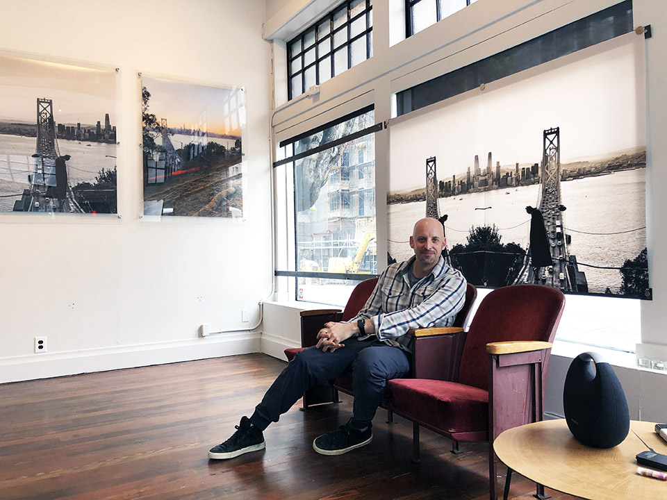 Christopher Callaway in front of his photographs at new gallery The Laguna 500. | Photo: Teresa Hammerl/Hoodline
