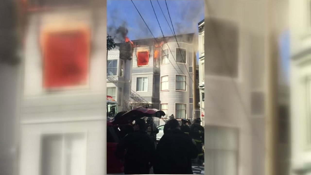 Flames are seen shooting from a top floor window of a home in San Francisco on Monday, Feb. 18, 2019.