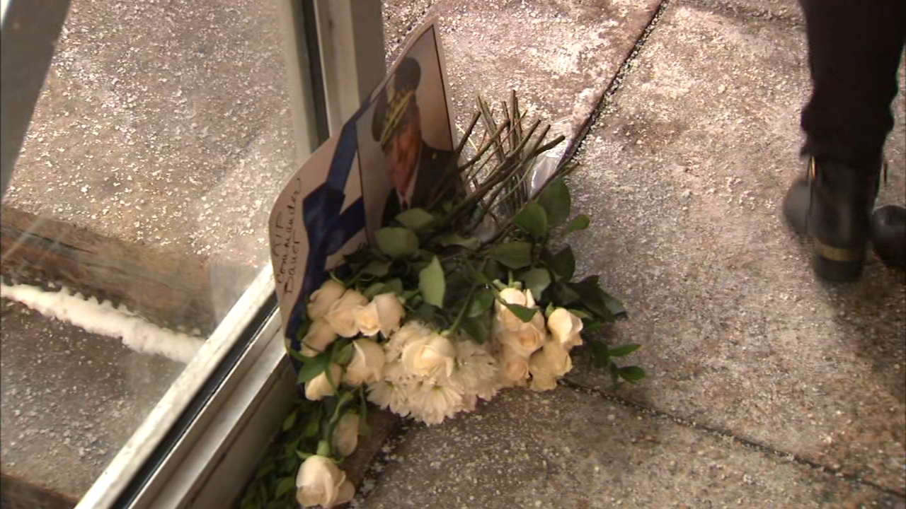 Family members of fallen Chicago police Cmdr. Paul Bauer laid flowers near the steps where he was fatally shot at the Thompson Center a year ago.