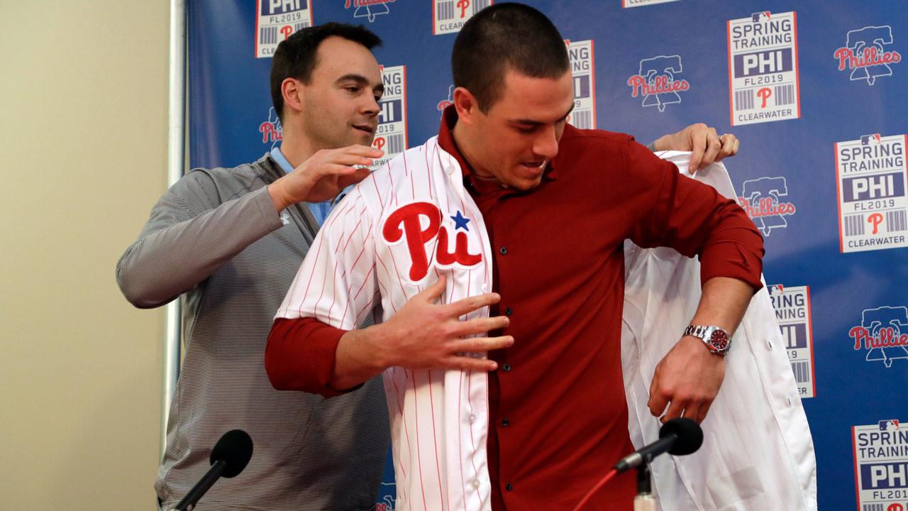 Philadelphia Phillies general manager Matt Klentak, left, helps catcher J.T. Realmuto put on his new uniform during a news conference.
