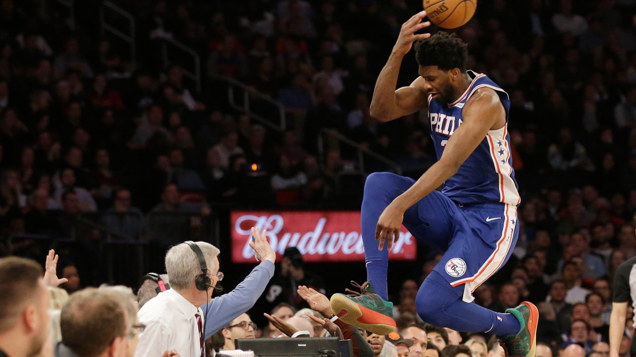 Philadelphia 76ers Joel Embiid leaps into the stands while chasing a loose ball during the second half of an NBA basketball game against the New York Knicks.
