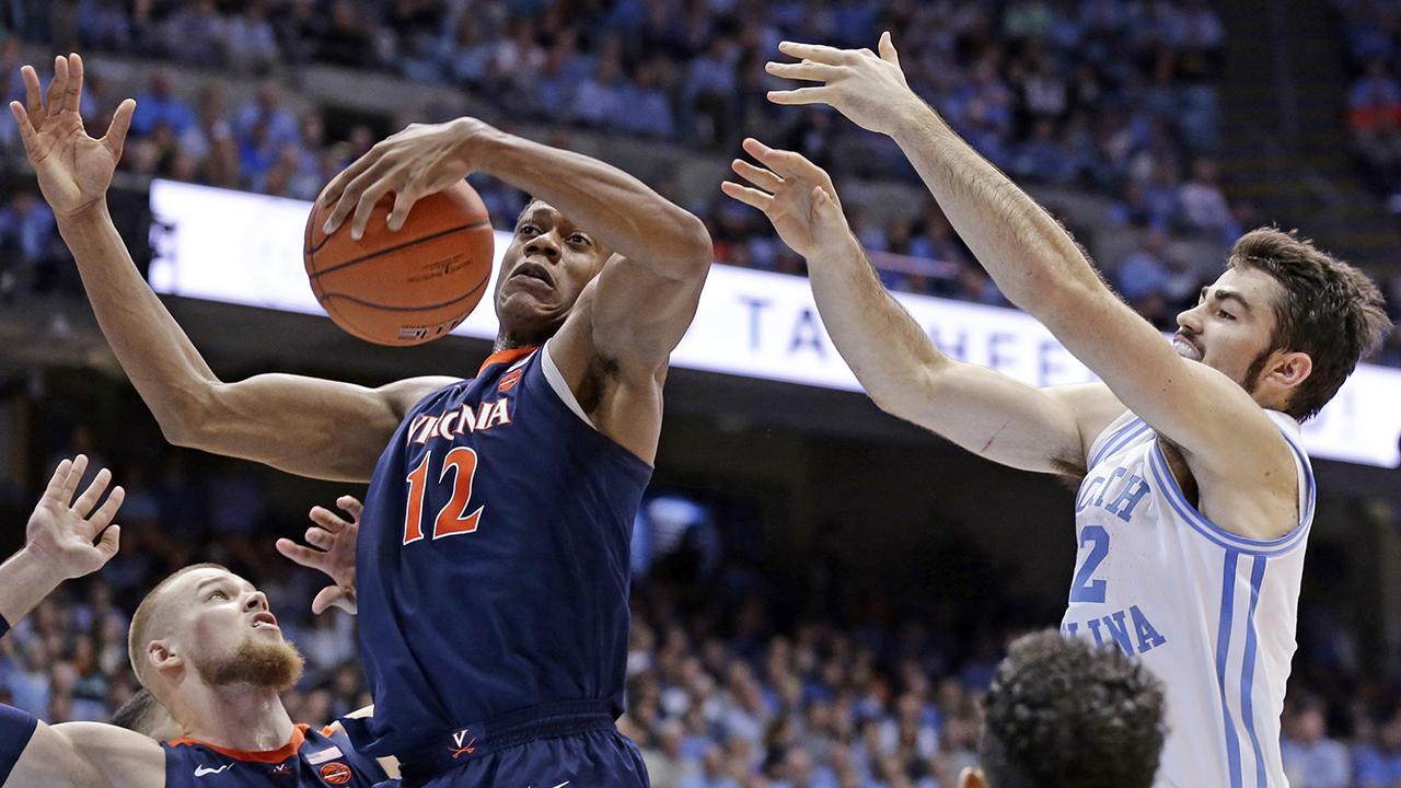 Virginias DeAndre Hunter rips a rebound as North Carolinas Luke Maye reaches in vain Monday night in Chapel Hill.