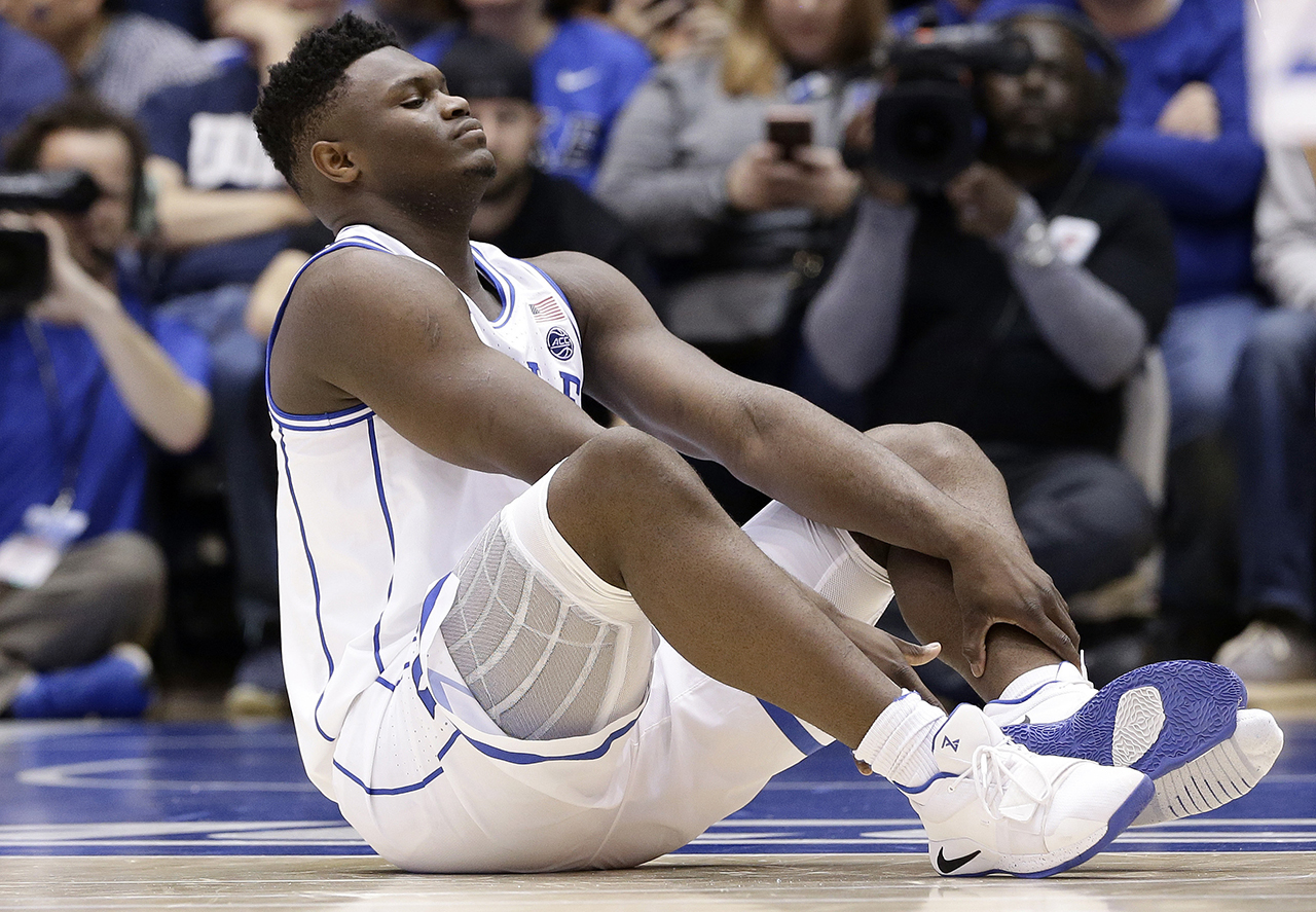 Dukes Zion Williamson sits on the floor following a freak injury just 36 seconds into the game.